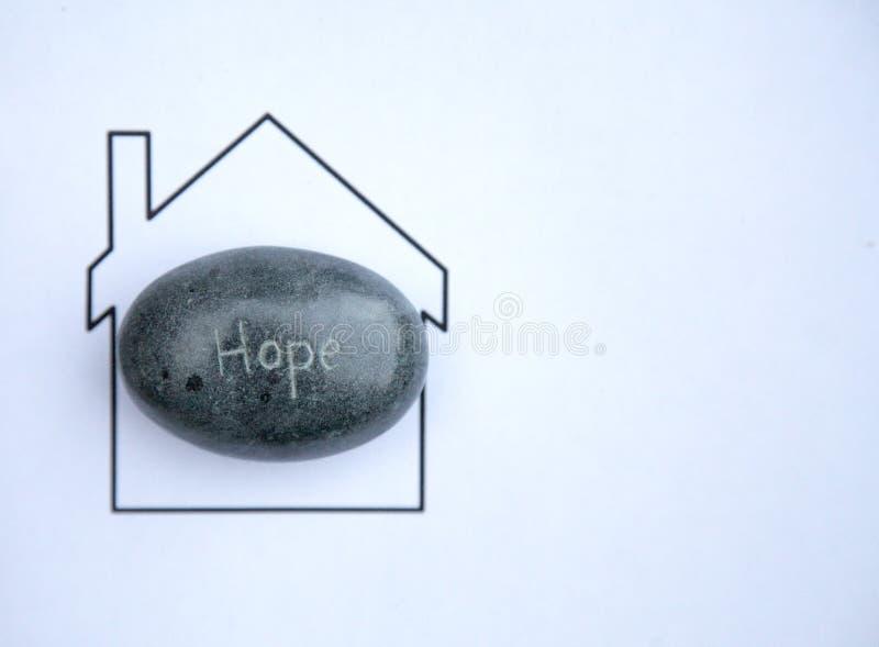 Изображение утеса выгравированного с надеждой слова над изображением дома стоковое изображение