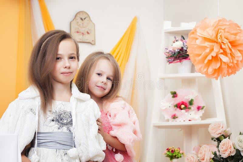Изображение ультрамодных сестер представляя в винтажном интерьере стоковые изображения