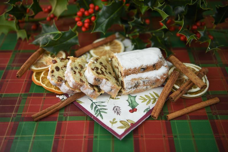 Изображение фотографии еды рождества с stollen листья и ягоды падуба отрезка ручек циннамона хлеба торта на зеленом красном кухон стоковые изображения rf