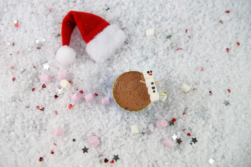 Изображение фотографии рождества при питье горячего шоколада и мини зефиры сформированные как снеговик клало в снег с шляпой Сант стоковая фотография rf