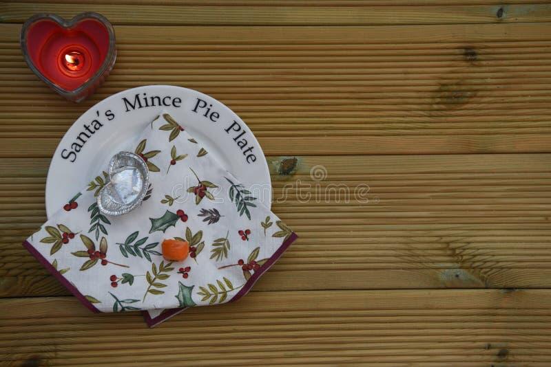 Изображение фотографии рождества Санты семенит плиту пирога показывая съеденную морковь от северного оленя и пустую плиту с свечо стоковые изображения