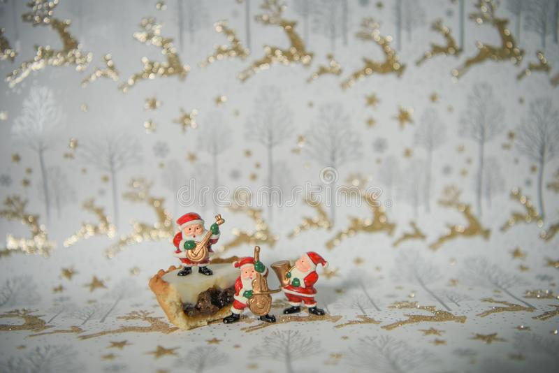 Изображение фотоснимка еды рождества с замороженный семенит пирог и мини музыку играя Санта Клауса на упаковочной бумаге северног стоковое фото