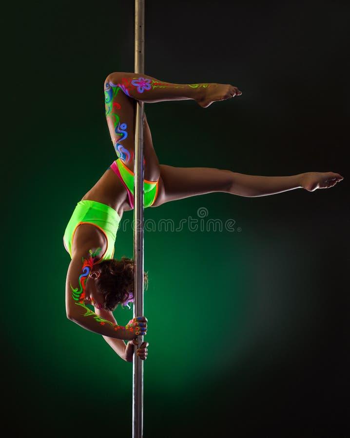 Изображение худенький висеть девушки вверх ногами на опоре стоковая фотография