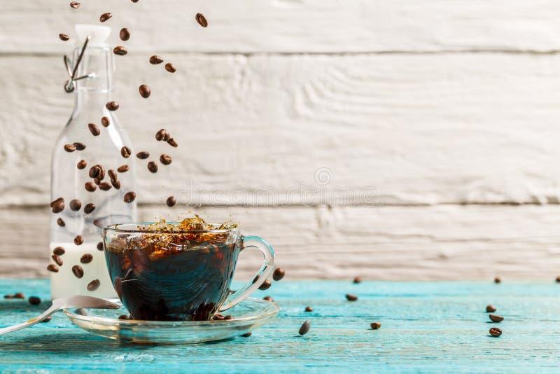 Изображение чашки кофе, кувшина молока с падая кофейными зернами стоковая фотография