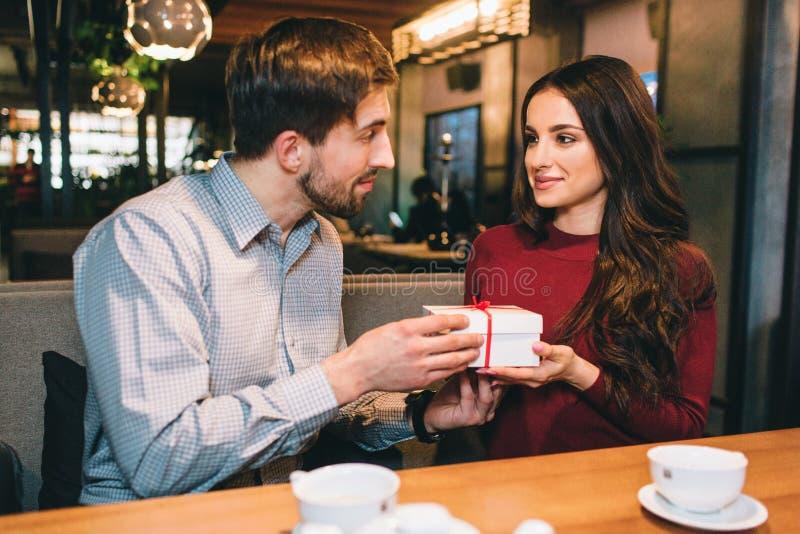 Изображение человека давая настоящий момент к женщине Они смотрят друг к другу и усмехаются немного Они sittin внутри стоковое изображение