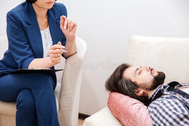 Изображение человека лежа на софе Он очень спокоен Гай держит его глаза закрытый Терапевт сидя близко к стоковые фотографии rf