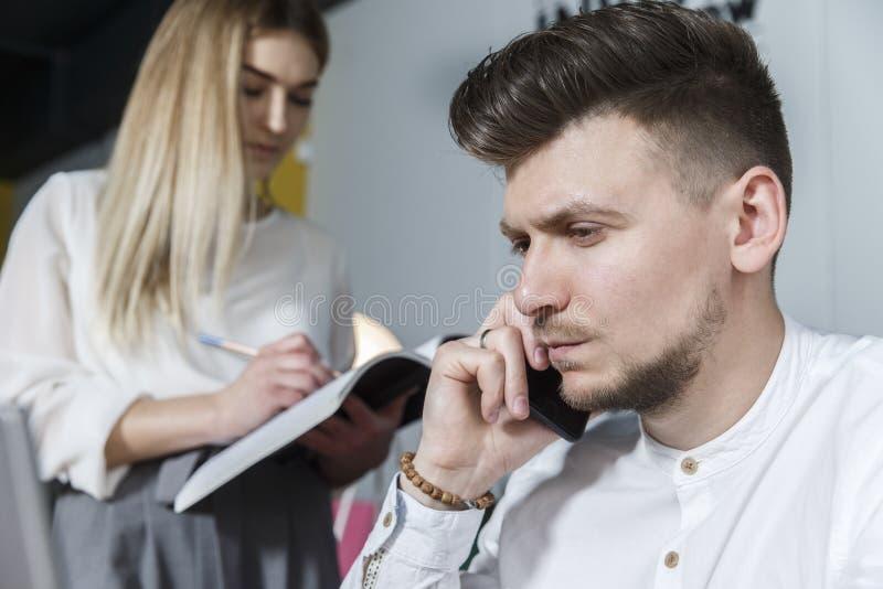 Изображение человека смотря вперед и говоря по телефону Он серьезен Девушка стоит кроме его и смотрит журнал r стоковые изображения rf