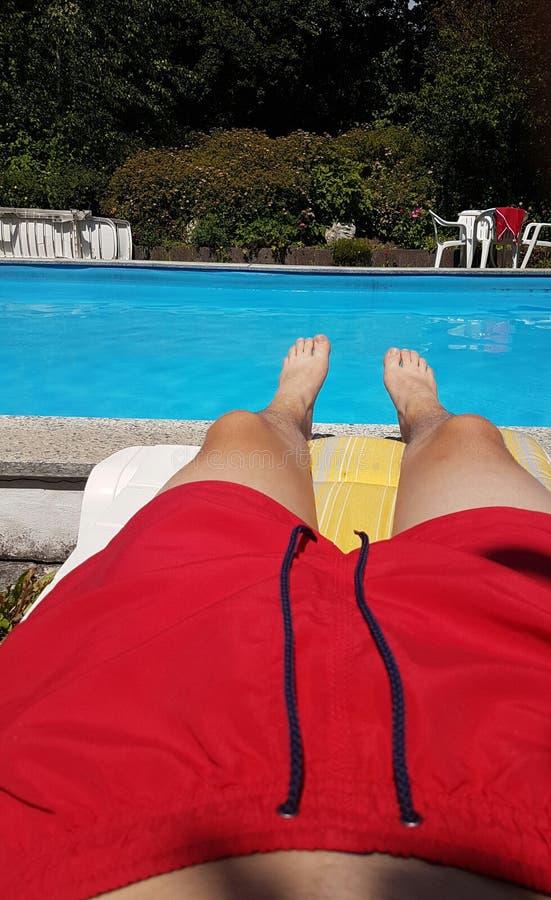 Изображение человека кладя на бассейн с красными купальщиками стоковое фото