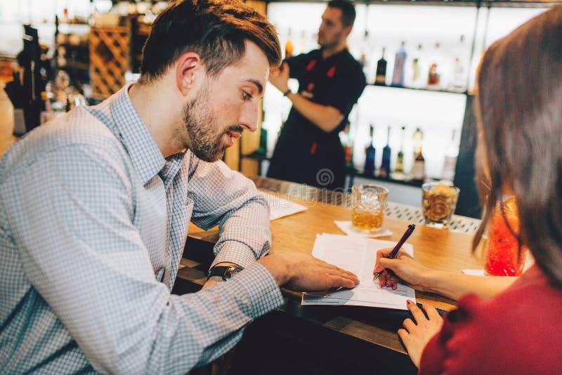 Изображение metting дела 2 людей Молодая женщина подписывает документы которые человек дал ей к знаку стоковые изображения