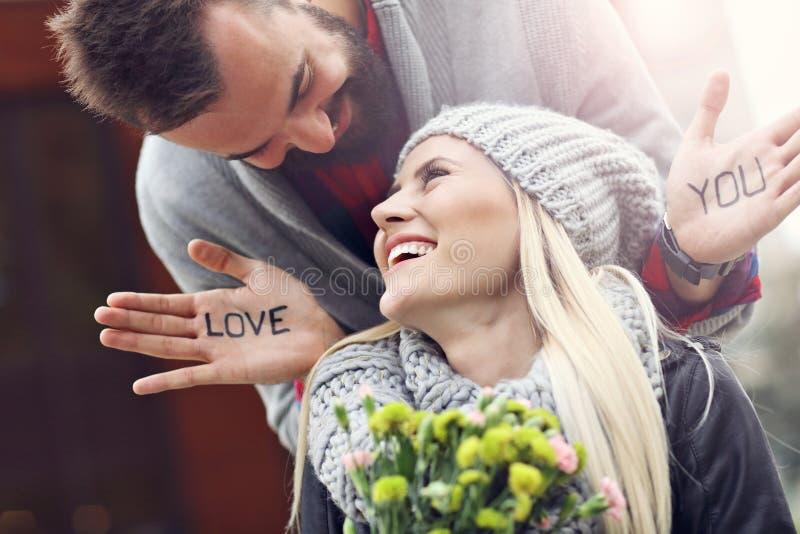 Изобразите показывать молодых пар при цветки датируя в городе стоковое изображение