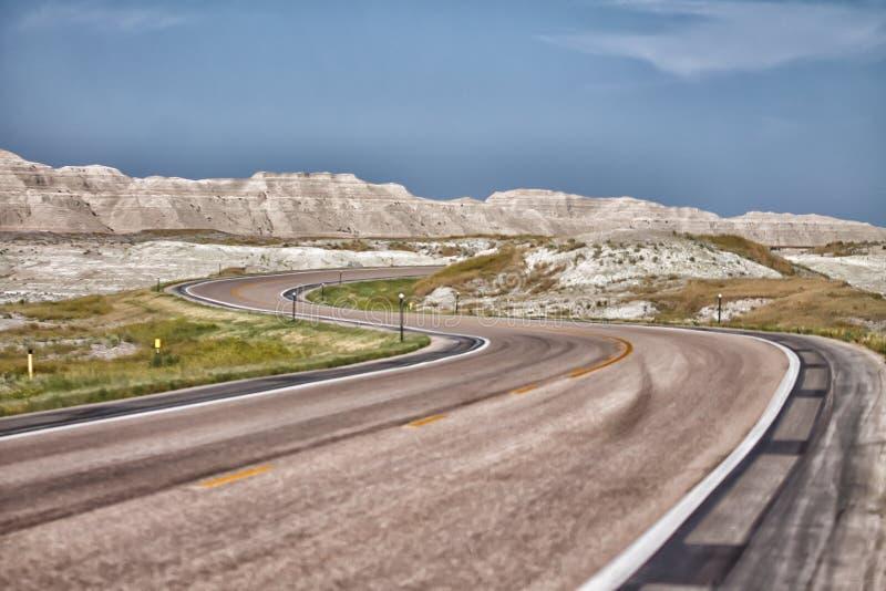 Изогнутый s вымостил дорогу через неплодородные почвы Южной Дакоты стоковое фото rf