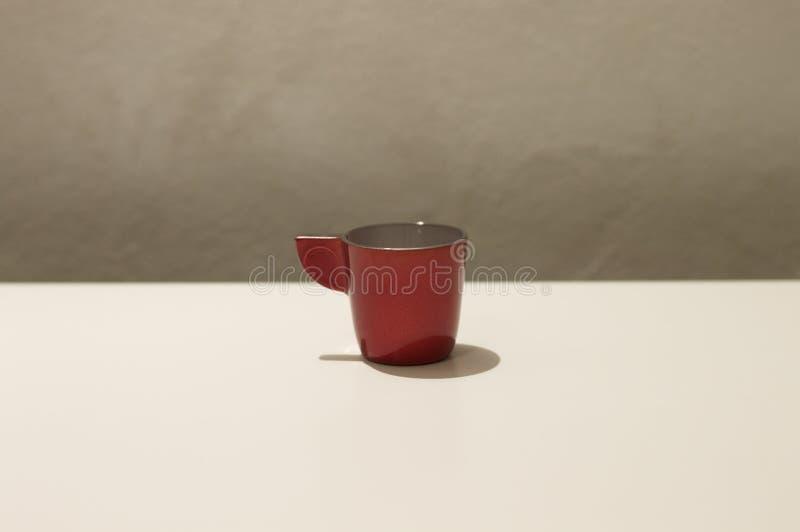 Изолированная красная кофейная чашка на белой таблице стоковая фотография