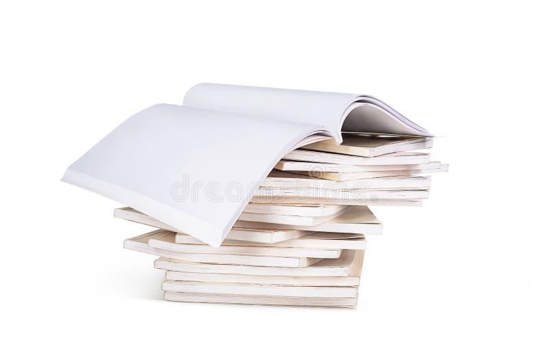 Изолированная куча книг с открытой книгой на верхней части, стоковое изображение