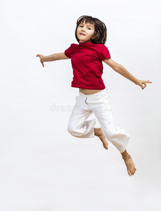 Изолированная счастливая маленькая девочка скача и летая для того чтобы выразить воображение стоковое изображение rf