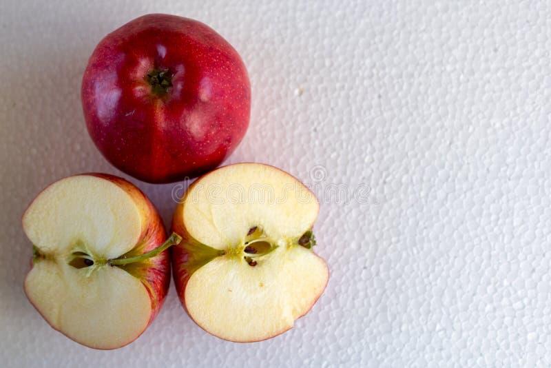 Изолированное красное яблоко и 2 половинных яблока на белой предпосылке стоковое изображение