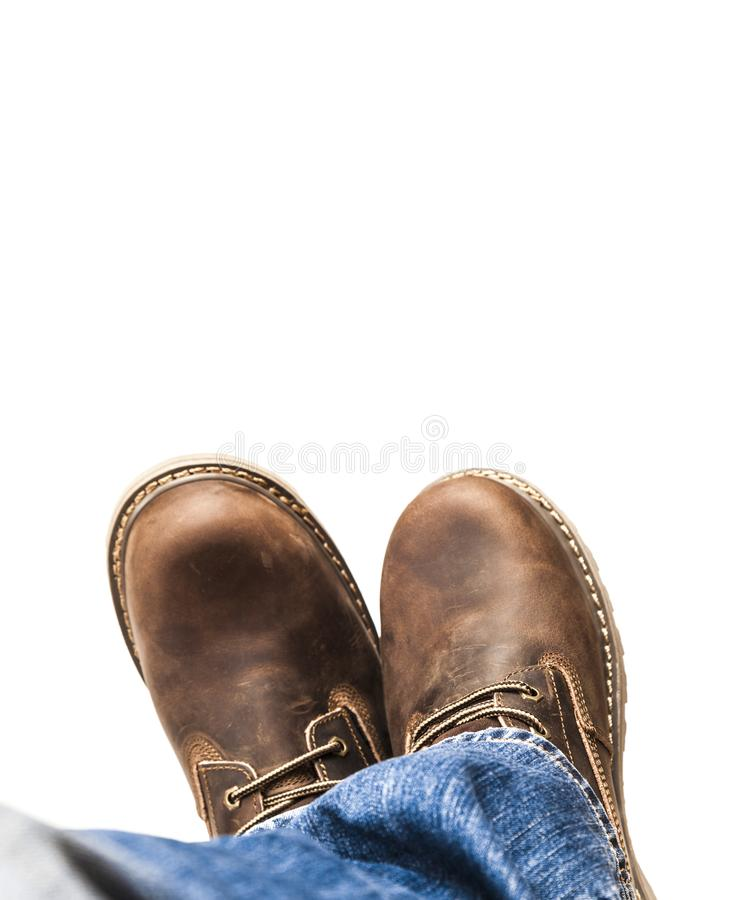 Изолированные ботинки коричневого цвета ` s людей и голубые джинсы стоковое фото
