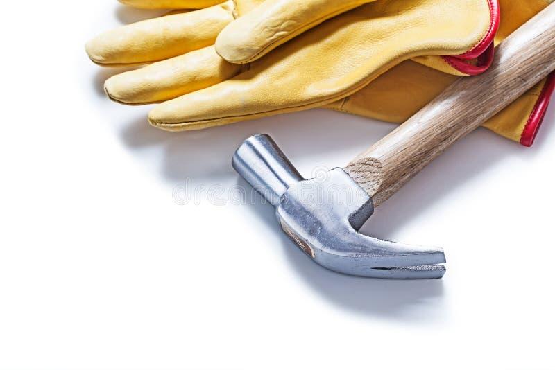 Изолированные молоток с раздвоенным хвостом и желтые кожаные перчатки стоковая фотография