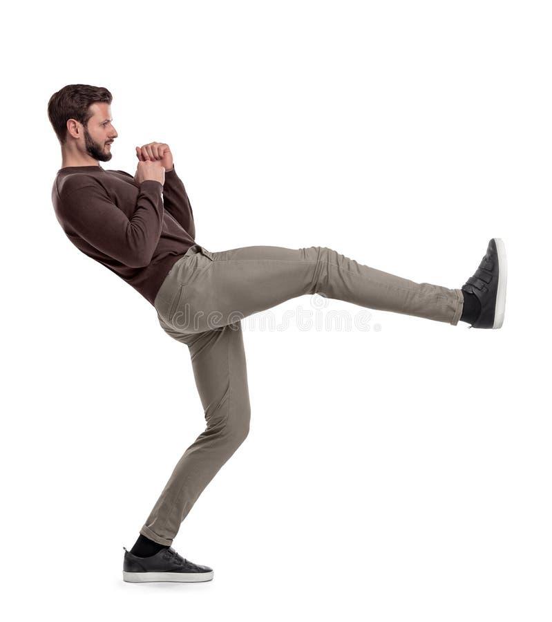 Изолированный бородатый человек в вскользь одеждах стоит на белой предпосылке в середине пинка ноги стоковые изображения