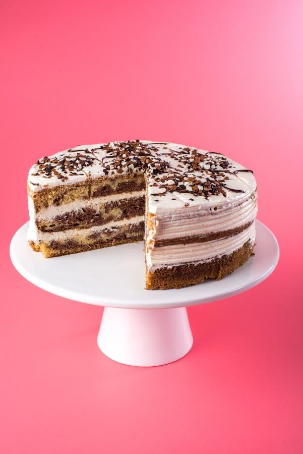 Изолированный домодельный наслоенный торт губки с белой сливк в деревенском стиле с отрезком вне соединяет на розовой предпосылке стоковая фотография rf
