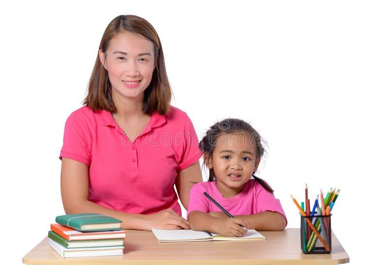 Изолированный ребенок молодого учителя помогая с записью урока на whit стоковая фотография