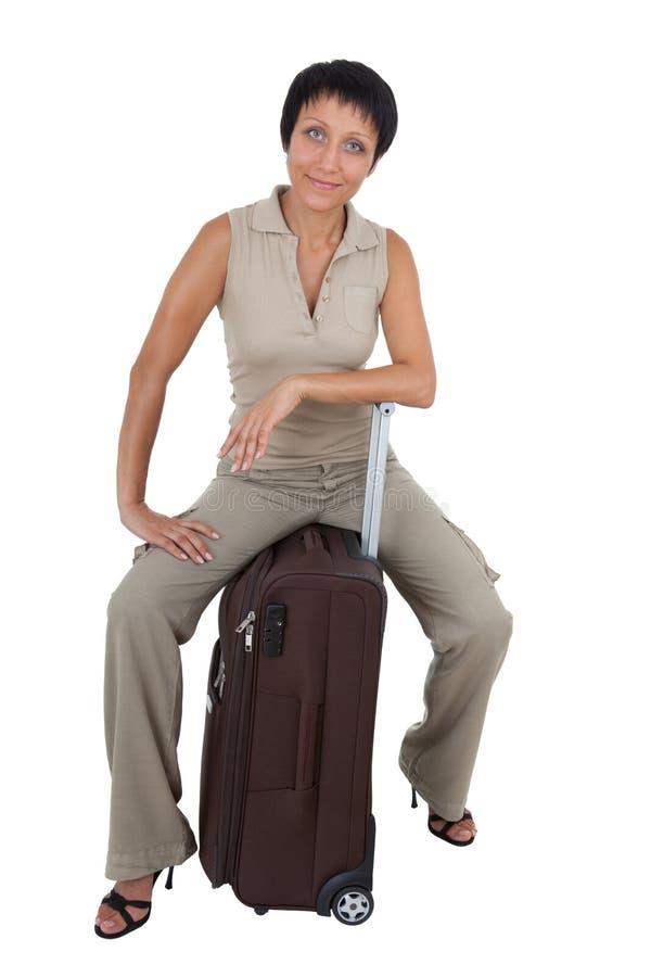 изолировано сидит детеныши женщины чемодана туристские стоковое изображение