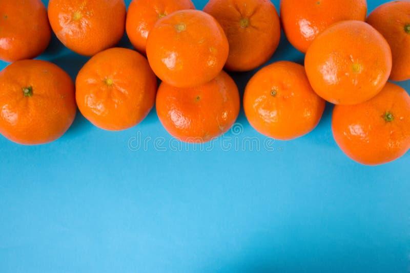 Изолированы свежие зрелые сочные мандарин или tangerines плодоовощ в апельсиновой корке на голубом взгляде столешницы Открытое по стоковое фото rf