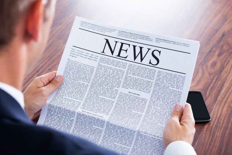 изолированная бизнесменом белизна чтения газеты стоковые фото