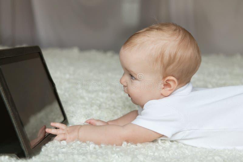изолированная девушка предпосылки младенца играющ белизну таблетки стоковые изображения
