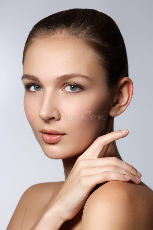 изолированная красоткой белизна портрета Красивая женщина спы касаясь ее стороне Совершенная свежая кожа Чисто девушка модели кра стоковое изображение