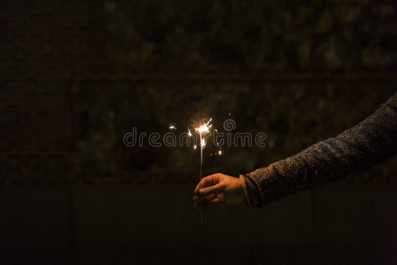 Изолированная рука женщины hoding искра на ноче стоковое изображение rf