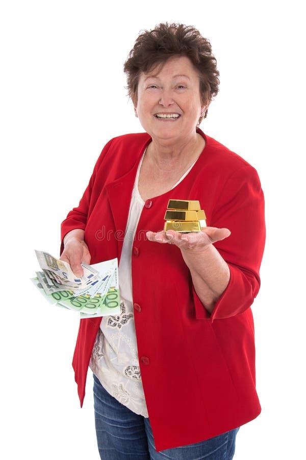Изолированная старшая женщина с деньгами и золотом: концепция для пенсии a стоковое фото rf