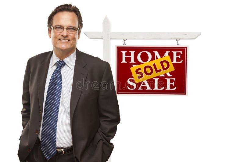 Изолированные бизнесмен и проданный домой для продажи знак недвижимости стоковое изображение rf