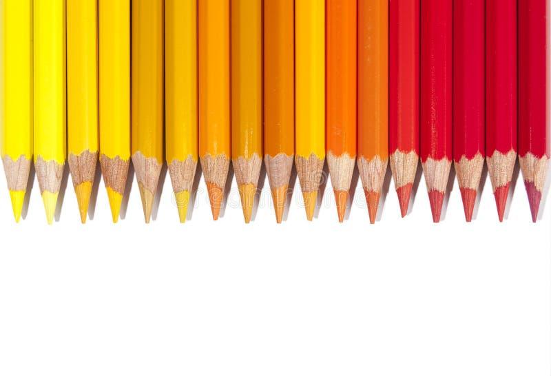 Изолированные красные желтые и оранжевые карандаши в линии стоковая фотография rf