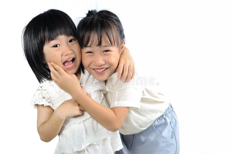 Изолированный обнимать 2 счастливый азиатский маленьких сестер стоковые фото