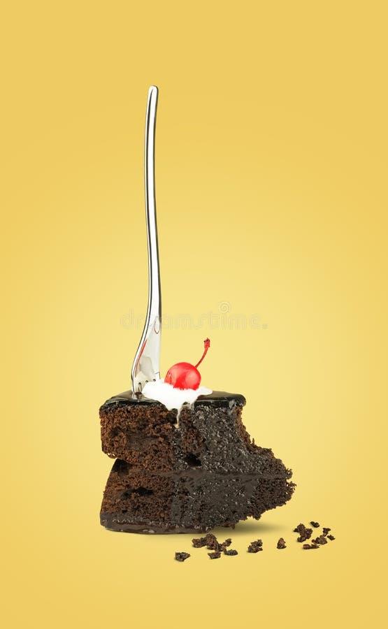 Изолированный торт вишни шоколада с вилкой от задней части на желтой предпосылке стоковые фото