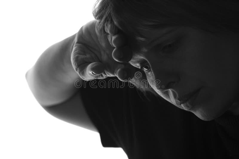 Изолированный черно-белый портрет утомленной женщины кладет ее руку к ее лбу стоковая фотография rf