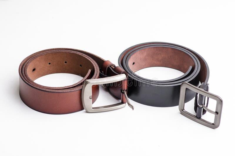 Изолируйте черный и коричневый кожаный пояс на белой предпосылке стоковое изображение rf