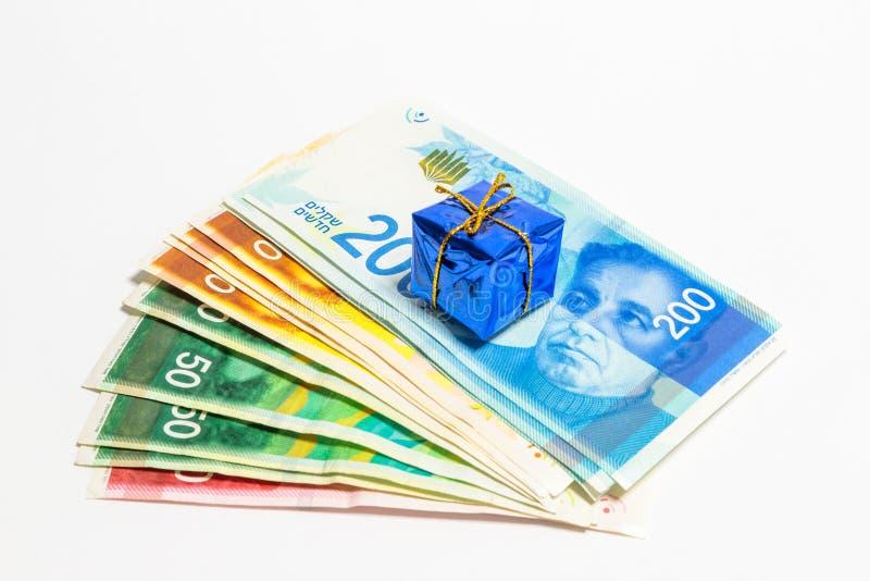 Израильский стог денег новых израильских банкнот различного значения в шекелях NIS при декоративная голубая коробка представляя п стоковые изображения