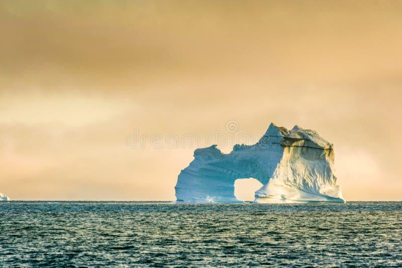 Изрезанный и мощный айсберг сидит самостоятельно в Северном океане стоковая фотография rf