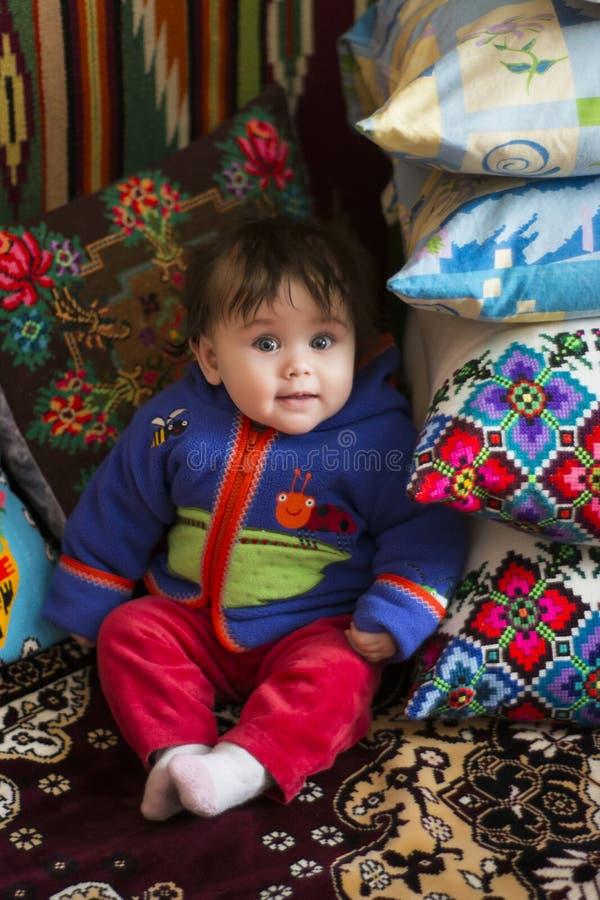 Изумительная маленькая девочка сидя в кровати на кровати с вышитыми подушками стоковые изображения rf
