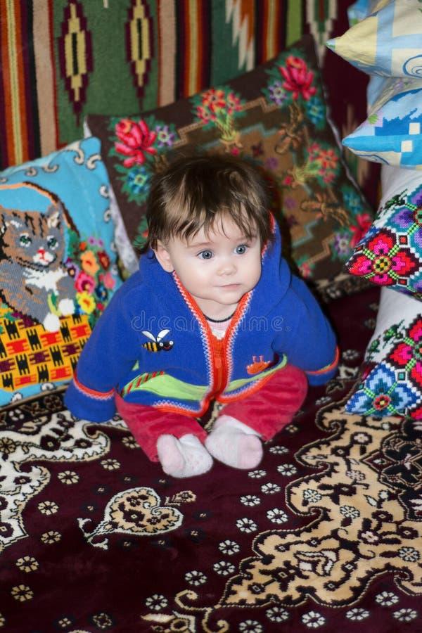 Изумительная маленькая девочка сидя в кровати на кровати с вышитыми подушками стоковые фото