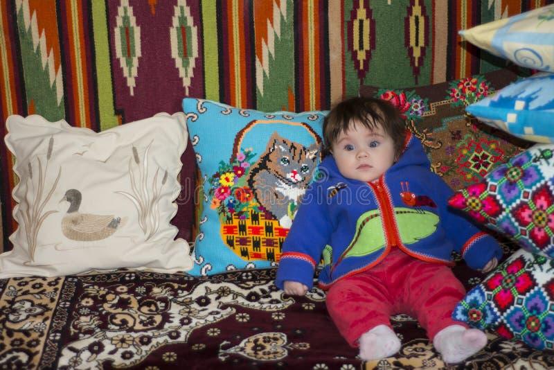 Изумительная маленькая девочка сидя в кровати на кровати с вышитыми подушками стоковые изображения
