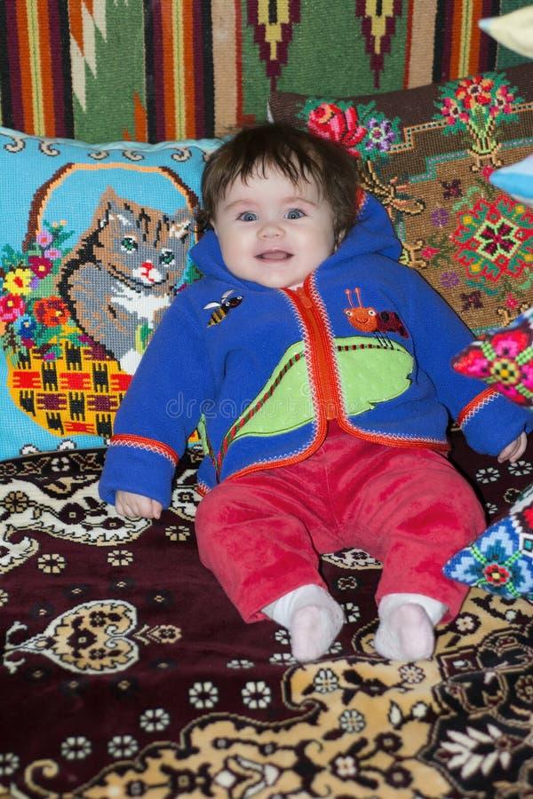 Изумительная маленькая девочка сидя в кровати на кровати с вышитыми подушками стоковая фотография rf