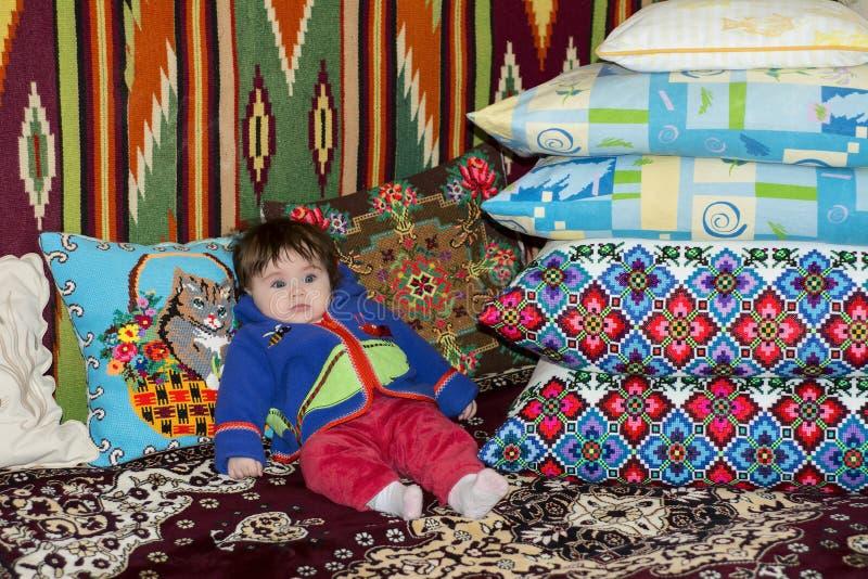 Изумительная маленькая девочка сидя в кровати на кровати с вышитыми подушками стоковое фото