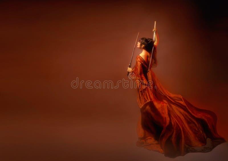 Изумительная темн-с волосами японская женщина самураев, маленькая девочка в светлом длинном красном порхая платье с открытым наза стоковые изображения rf