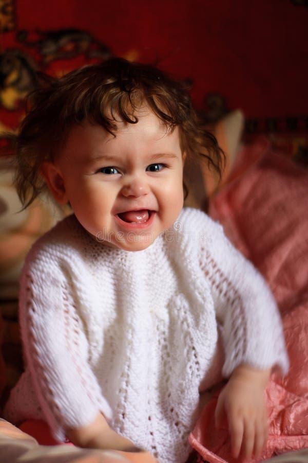 Изумительная украинская девушка в белом свитере смотря очаровательный и смеяться над стоковое фото rf