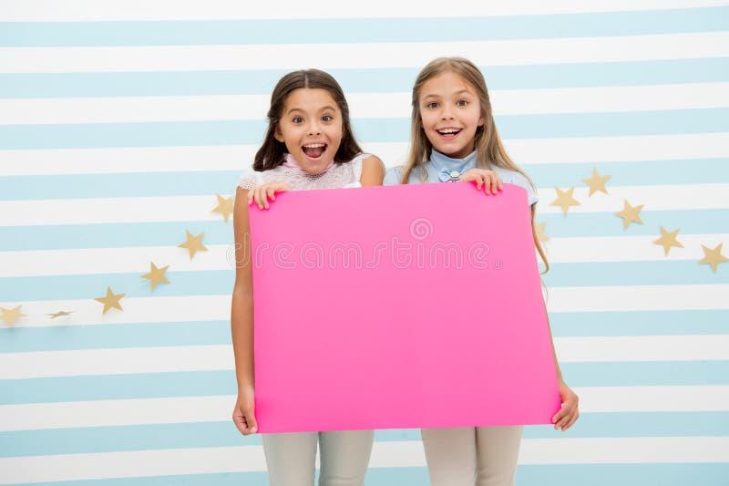 Изумительные удивительно новости Знамя объявления владением девушки Дети девушек держа бумажное знамя для объявления Дети счастли стоковые фотографии rf