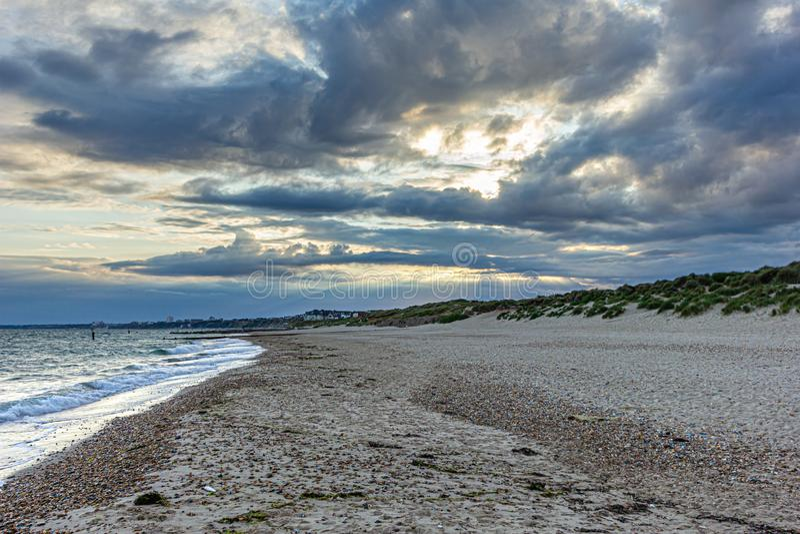Изумительный взгляд бурного неба с солнцем и лучем света через впечатляющие темные и светлые облака вдоль песчаного пляжа, изменч стоковое изображение rf