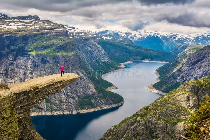 Изумительный взгляд природы с Trolltunga и девушка стоя на ем стоковое фото