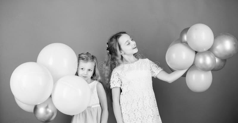 Изумительный день с полным потехи Маленькие девочки празднуя годовщину дня рождения с воздушными шарами Прелестные дети наслаждаю стоковые фото
